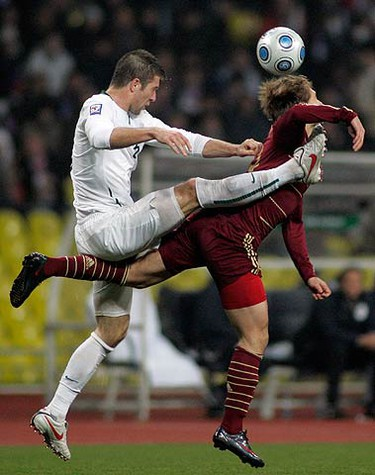 Russia's Roman Pavlyuchenko (R) fights for the ball with Slovenia's Miso Brecko during their 2010 World Cup European qualifying playoff in Moscow on Nov. 14, 2009. (REUTERS)