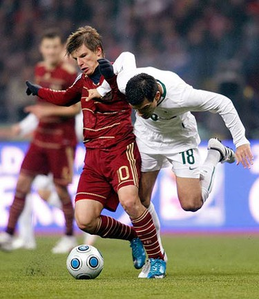 Russia's Andrei Arshavin (L) fights for the ball with Slovenia's Aleksander Radosavljevic during their 2010 World Cup European qualifying playoff in Moscow on Nov. 14, 2009. (REUTERS)