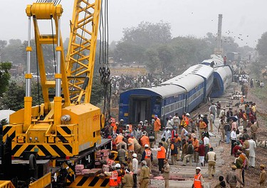 Onlookers stand beside derailed carriages of a passenger train near Banshkov village, about 40 km (25 miles) south of Jaipur on Nov. 14, 2009. At least seven people were killed and 25 injured when a New Delhi-bound train derailed near Jaipur. (REUTERS)