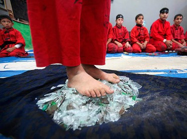 A Palestinian boy stands on broken glass during a class at the Red Dragon martial arts club in Beit Lahiya in the northern Gaza Strip on Nov. 12, 2009. (REUTERS)