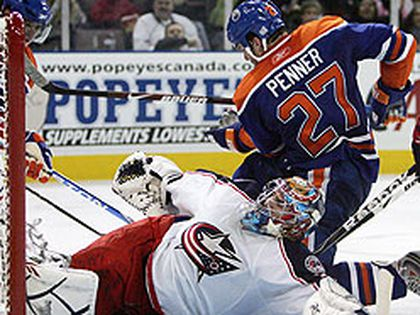 Oilers winger Dustin Penner crashes the net against Columbus Blue Jackets goalie Mathieu Garon during an October game at Rexall Place. Penner, who is leading Edmonton in scoring, will likely be given special attention by the Ottawa Senators tonight.