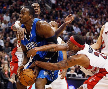 Orlando Magic centre Dwight Howard (L) is double teamed by Toronto Raptors forwards Chris Bosh and Antoine Wright (R) during the second half of their NBA basketball game in Toronto on Nov. 1, 2009. (REUTERS)
