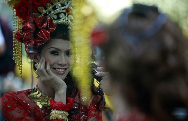 A contestant is reflected in a mirror as she has makeup applied in the dressing room before competing in the Miss International Queen 2009 transsexual beauty pageant in the Thai resort city of Pattaya, about 150 km (93 miles) southeast of Bangkok, on Oct. 31, 2009. (REUTERS)