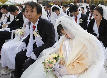A bride takes a nap during a mass wedding ceremony of the Unification Church at Sun Moon University in Asan, south of Seoul Oct. 14, 2009. REUTERS/Lee Jae-Won