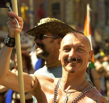 A happy marcher decked out in his finest piercings and chains, helps carry a banner down Yonge St. in 2001. (GREG HENKENHAF, Sun Media)