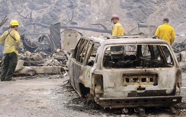 Firefighters look over debris in Big Tujunga Canyon after the Station Fire burned the area near Los Angeles August 30, 2009. The wildfire burning out of control in the mountains of Los Angeles doubled in size overnight on August 31, 2009 and torched more structures on its march toward rural communities, officials said.  Picture taken August 30, 2009.   REUTERS/Gene Blevins