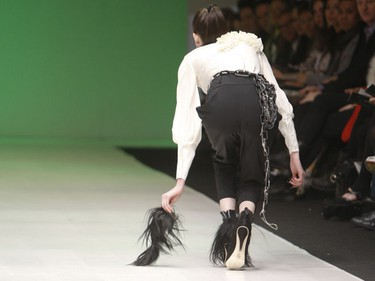 "Toronto designer Nada Shepherd's sleek futuristic designs entitled ""Utopia"" took to the main stage at Toronto's LG Fashion Week held at Nathan Phillips Square. (Pictured) One of the models picks up a shaggy anklet that came off her spiked booties. (SUN MEDIA/Jack Boland)"