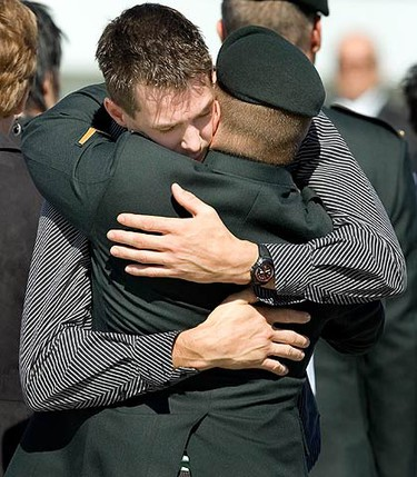 The brother of Private Jonathan Couturier embraces an unidentified soldier on the tarmac at the Canadian Forces Base Trenton on Sept. 20, 2009. Pte. Couturier was killed when an improvised explosive device exploded near his vehicle in Panjwai District, southwest of Kandahar City on Sept., 17, 2009. (REUTERS)