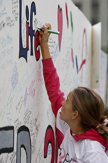 A participant signs a large mural with a message of courage, hope and love. An estimated 30,000 people participated in the 18th annual Canadian Breast Cancer Foundation CIBC Run for the Cure in Toronto started at Nathan Phillips Square. The five and one kilometre run/walk has participants raise funds in support of breast cancer research, education and awareness initiatives. The event takes place in 56 communities across the country. (JACK BOLAND, Sun Media)