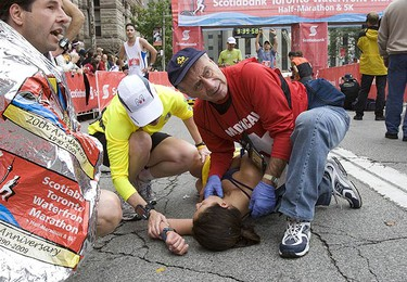 Marathon participants are helped as they cross the finish line at the Toronto Waterfront Marathon held in downtown toronto on Sept. 27, 2009. (STAN BEHAL, Sun Media)