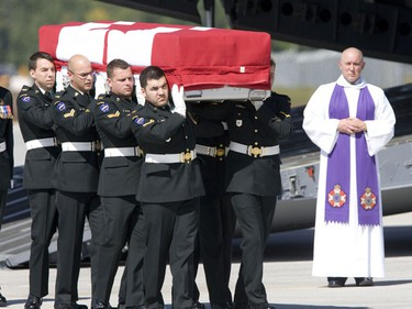 Soldiers carry the flag draped casket of Major Yannick Pepin from a C-17 Globemaster at CFB Trenton on Wednesday afternoon. (PETE FISHER/Sun Media)