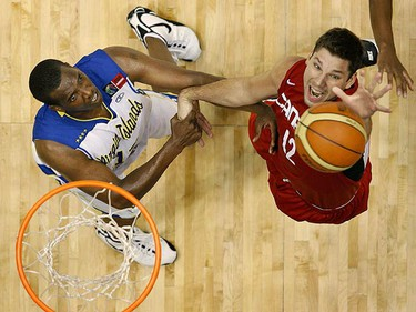 Canada's Jesse Young (R) is grabbed by Calvert White of the Virgin Islands during the second half of their men's FIBA Americas Championship qualifying round basketball game in San Juan on Aug. 28, 2009. (REUTERS)