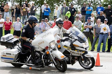 A Toronto Police officer (riding an OPP bike) competes against a Quebec Provincial Police officer in the Crash Competition during Canada's 911 Ride Foundation's Charity Motorcycle ride. The foundations mission is to host an annual police escorted motorcycle ride to raise funds and awareness to help families of fallen emergency service personnel and children who are victims of crime. (GREG HENKENHAG, Sun Media)