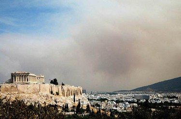 A thick cloud of smoke from a forest fire rises over Athens' Acropolis on Aug. 22, 2009. A large wildfire raged out of control on the outskirts of Athens on Saturday, burning several homes and thousands of acres of forest.  (REUTERS)