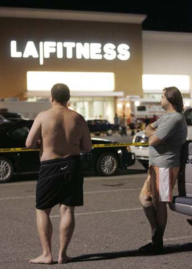 Men wait behind police lines outside the LA Fitness gym in Bridgeville, Pennsylvania Aug. 4, 2009, while police investigate a shooting that happened earlier in the evening. At least three people, plus the gunman, were shot and killed during a shooting spree at the fitness center near Pittsburgh, according to media reports. (Jason Cohn/REUTERS)