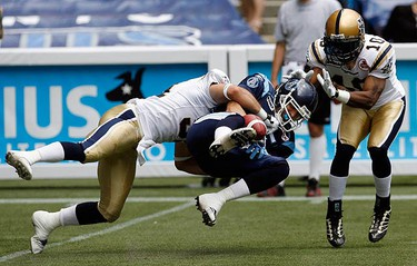 Toronto Argonauts' wide receiver Tyler Scott (C) fumbles the ball while being tackled by Winnipeg Blue Bombers defenders Ian Logan (L) and Keyuo Craver (R) during the first half of their CFL football game in Toronto on August 1, 2009. (REUTERS)