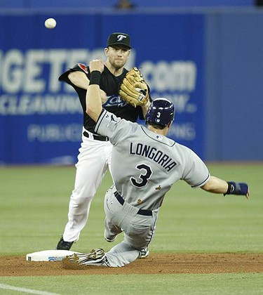 Toronto Blue Jays shortstop Aaron Hill, left, forces Tampa Bay Rays' Evan Longoria out at second base before throwing to first to double up Ben Zobrist during the fourth inning of an MLB game in Toronto on July 26, 2009. (ALEX UROSEVIC, Sun Media)