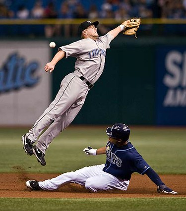 Toronto Blue Jays' Aaron Hill (L) reaches for a high throw from catcher Rod Barajas as Tampa Bay Rays' Carl Crawford steals second base during an American League MLB baseball game in St. Petersburg, Florida on July 9, 2009.  (REUTERS)