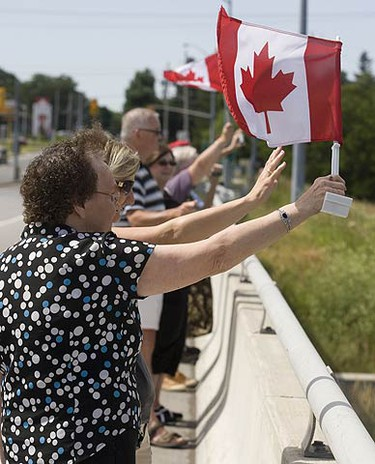 On the County Road 28 bridge in Port Hope supporters of the ride waved Canadian flags from the bridges. (PETE FISHER, Sun Media)