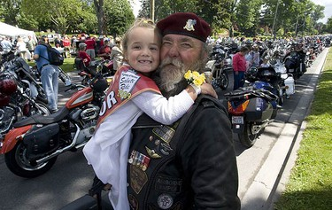 Ride ambassador Dakota Lee Allen hugs her friend and Veteran Paul Cane who is the National President of The Canadian Army Veterans motorcycle unit.  (PETE FISHER, Sun Media)