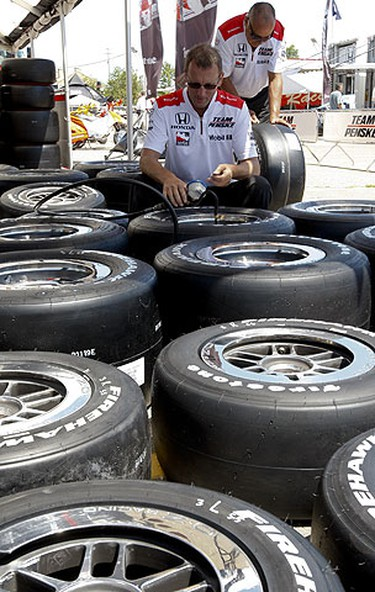 John Turpin (front) and Damon Lopez (rear) of Team Penske check out the tires for Helio Castroneves and Scott Briscoe, July 9, 2009. (Jack Boland/Sun Media)