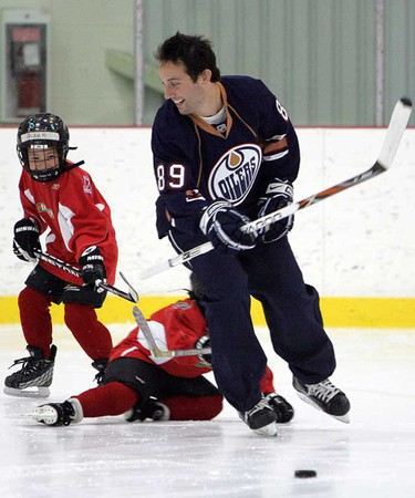 Edmonton Oiler Sam Gagner gets suited up to practice with Cayne Yacey, 6, at Millenium Place in Sherwood Park.  Yacey won the Kraft Delissio Ultimate Hockey Practice contest, which awarded two Canadians a private practice with an NHL star. (Amber Bracken/Sun Media)
