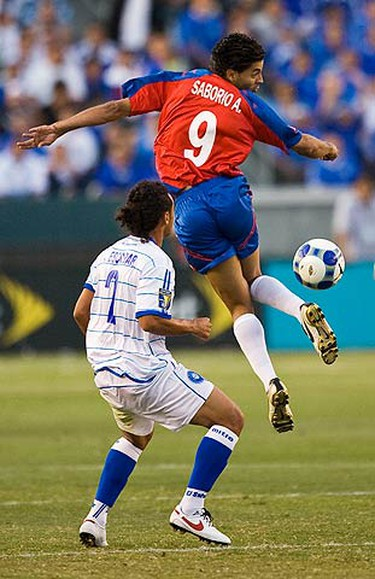 Costa Rica's Alvaro Saborio (R) twists backward to kick the ball away from El Salvador's Alexander Escobar in the first half of their CONACAF Gold Cup soccer match in Carson, California on July 3, 2009. (REUTERS)