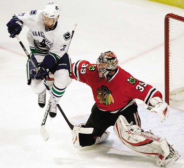 Chicago Blackhawks goalie Nikolai Khabibulin makes a save as Vancouver Canucks left wing Daniel Sedin jumps up in front of him in the first period during Game 6 of their NHL Western conference semi-final hockey playoff in Chicago, May 11, 2009. (REUTERS/Frank Polich)