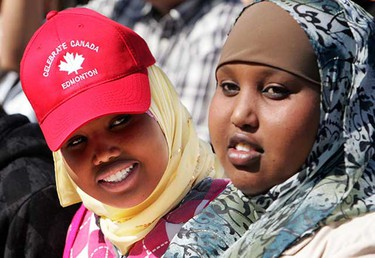 Hodn Khalif, 16, wears a Celebrate Canada hat while sitting with Ifrah Khalif, 18, after becoming a new Canadian during Canada Day festivities.  Both girls emigrated from Somalia. (Amber Bracken/Sun Media)