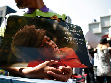 A fan holds a poster while he waits in line to enter the Michael Jackson public memorial at the Apollo Theater in New York June 30, 2009. The Apollo will welcome fans 600 at a time to enter the theater to pay their respects, hear Jackson's music spun by New York DJs and see a a video tribute to the late pop star. (REUTERS)