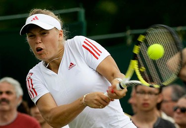Caroline Wozniacki, of Denmark, returns the ball to Sabine Lisicki, of Germany, during their match at the Wimbledon tennis championships on June 29, 2009. (REUTERS)