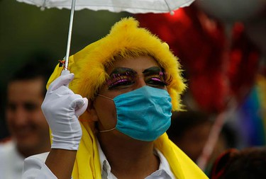 An LGBT (lesbian, gay, bisexual and transgender) rights activist, wearing a face mask, takes part in a pride parade in Mexico City on June 20, 2009. (REUTERS)