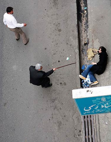 A man with a cane gestures towards a woman on the ground during protests in central Tehran on June 14, 2009. Defeated candidate Mirhossein Mousavi demanded that Iran's presidential election be annulled and urged more protests. (REUTERS)