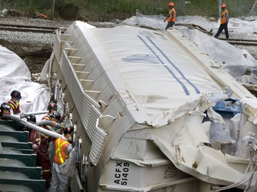 Work crews clean up after Friday's train derailment in Oshawa. This morning a new track was laid and one of the first trains since the derailment slowly passes the wreckage hauled off to the side.  (SUN MEDIA/Stan Behal)