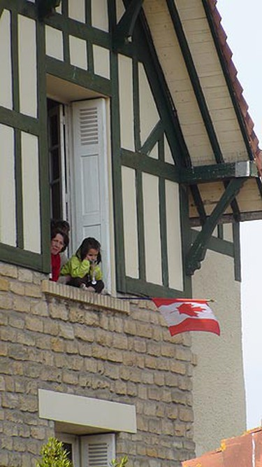 A French family flies a Canadian flag during a D-Day ceremony, Friday, June 5, 2009.  (KATHLEEN HARRIS/SUN MEDIA)