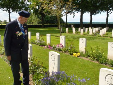 A war veteran pays respects to a friend's grave in Normandy, France. (KATHLEEN HARRIS/SUN MEDIA)