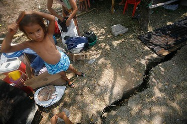 A boy stands near a crack on the ground in El Progreso. A powerful magnitude-7.1 earthquake shook Honduras knocking down homes and causing damage in Guatemala on May 28, 2009. (REUTERS)