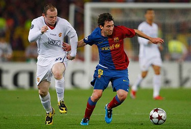 Manchester United's Wayne Rooney (L) challenges Barcelona's Lionel Messi during their Champions League final soccer match at the Olympic Stadium in Rome on May 27, 2009. (REUTERS)