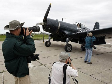 Photographers swarm the vintage Corsair WWII plane that just landed at the Wings and Wheels Heritage Festival on May 22, 2009. (MICHAEL PEAKE, Sun Media)