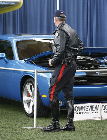 A member of the Toronto Police Winged Wheels motorcycle demonstration team has a look at one of the car exhibits at the Wings and Wheels Heritage Festival on May 22, 2009. (MICHAEL PEAKE, Sun Media)