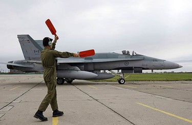 """Paul """"Skippy"""" Dimitriou guides in the CF-18 fighter jet, that landed from Bagotville, Quebec, at the Wings and Wheels Heritage Festival on May 22, 2009. (MICHAEL PEAKE, Sun Media)"""