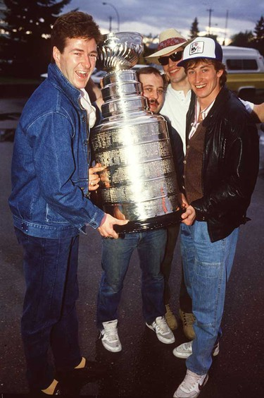 """Edmonton Oilers' Equipment Manager Lyle """"Sparky"""" Kulchisky (centre) and the Stanley Cup after leaving David's Restaurant in Edmonton Alberta on May 21, 1984. Also in picture are Oilers Kevin Lowe (left), Mark Messier (background) and Wayne Gretzky (Right). (Sun file photo)"""