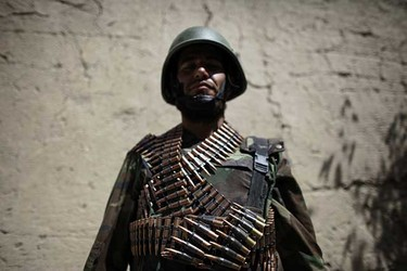 May. 16: An Afghan national army soldier poses with his ammunition during a special operation at Sanjaray in Kandahar Province. (REUTERS/Jorge Silva)