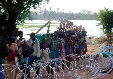 """This photograph released by the Sri Lankan military May 17, 2009 shows what the army says are civilians walking across a lagoon from inside the """"No Fire Zone"""" where government troops have the Tamil Tiger rebels surrounded for the final battle in a quarter-century conflict. (REUTERS)"""