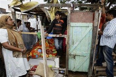 """""""Slumdog Millionaire"""" child star Azharuddin Mohammed Ismail, center, stands amid the remains of his demolished home in Mumbai, India, Thursday, May 14, 2009. City workers bulldozed the home of Azharuddin Thursday as part of the demolition of dozens of shanties in a Mumbai slum.(AP Photo/Gautam Singh)"""