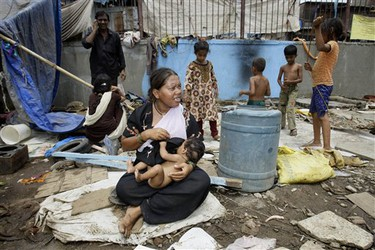 """A woman feeds her child as she sits among the debris of her shanty, part of the neighborhood of """"Slumdog Millionaire"""" child star Azharuddin Mohammed Ismail, unseen, that was demolished in Mumbai, India, Thursday, May 14, 2009. City workers bulldozed the home of Azharuddin Thursday as part of the demolition of dozens of shanties in a Mumbai slum.(AP Photo/Gautam Singh)"""