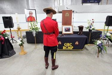Cpl. Wayne Oakes looks over pictures and flowers laid out for RCMP Constable James Lundblad, prior to Lundblad's Regimental Funeral Service in Valleyview, Alberta. Photo by David Bloom/Sun Media