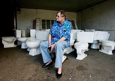 Lynn Karpetz waits for a taxi on a collection of toilets outside of the building she lives in at 118-19 106 Street. The toilets have been removed from many of the units, which are under renovation, but many of the sewage lines have not been capped in the interim. ((Amber Bracken/Sun Media))