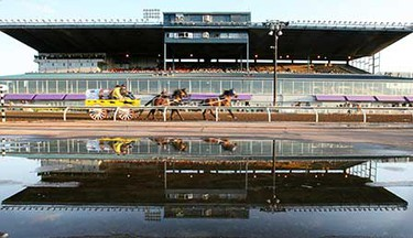 Shane Cartier, in the Canadian Western Bank sponsored wagon, and the Grandstands are reflected in a puddle as they warm up for the fourth heat during the WPCA Dodge World Championship chuckwagon races at Northlands. ((Amber Bracken/Sun Media))