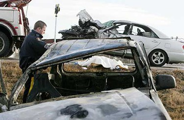 The body of a 71-year old male driver, from Alliance, Alta., is framed in the window of his burnt out 1991 Ford Explorer as the other vehicle, a 2004 Toyota Camry is towed away and RCMP investigate the scene of the two vehicle head on collision on Highway 21 south of Highway 625, Nov. 12. ((Amber Bracken/Sun Media))